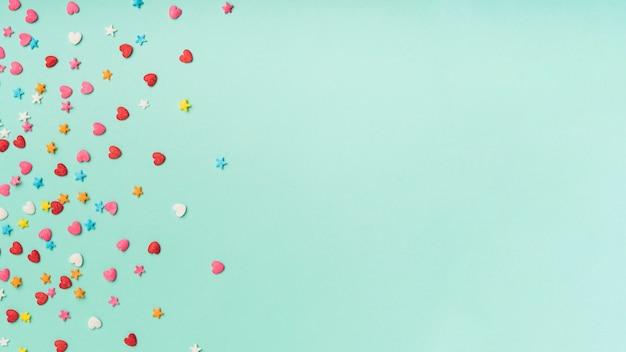 Coriandoli di stelle e cuori su uno sfondo turchese con spazio di copia