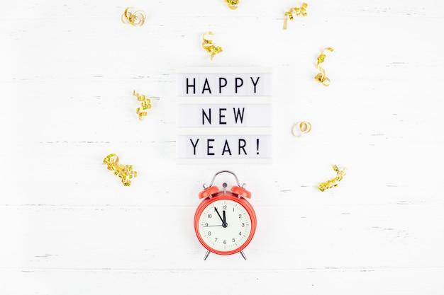 Coriandoli dorati della sveglia della composizione del nuovo anno
