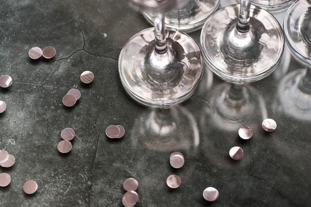 Coriandoli e bicchieri di vino d'argento su fondo concreto