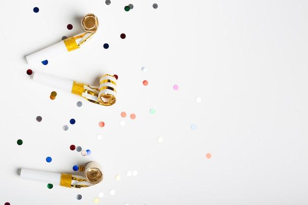 Coriandoli e fischietti di festa con spazio di copia
