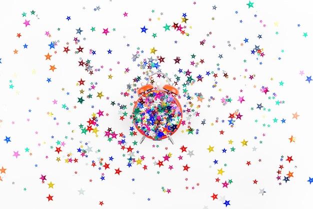 Coriandoli festivi della stella con il concetto rosso della sveglia