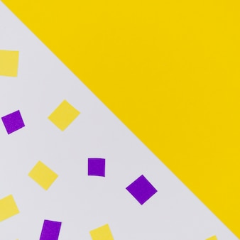 Coriandoli gialli e viola con spazio di copia