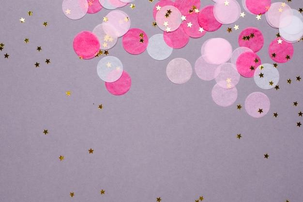 Coriandoli rosa con stelle d'oro su grigio con copyspace
