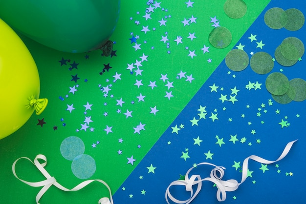 Coriandoli stelle e palloncini su sfondo colorato