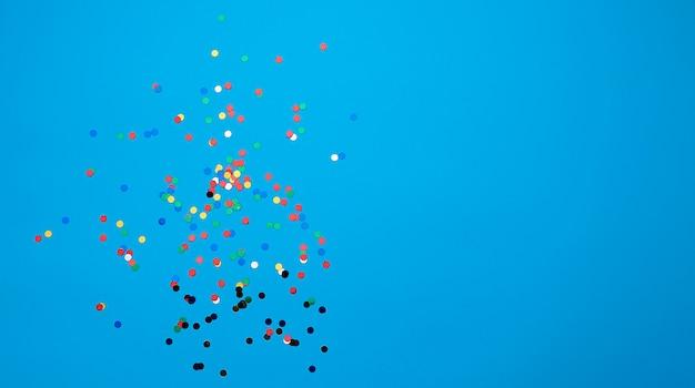 Coriandoli tondi multicolori lucidi sparsi su uno sfondo blu, sfondo festivo per il compleanno