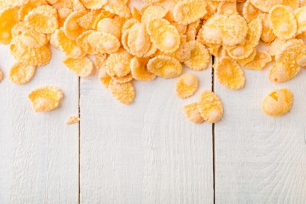 Corn flakes su superficie di legno bianca,
