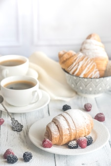 Cornetti con bacche fresche e due tazze di caffè