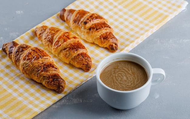Cornetti con caffè su intonaco e strofinaccio da cucina,