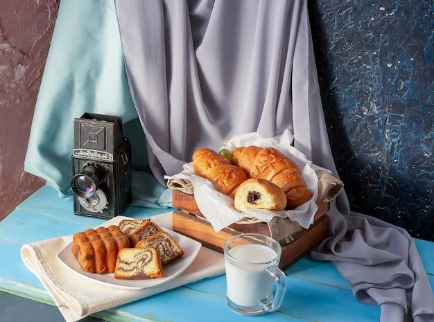 Cornetti con crema al cioccolato e un bicchiere di latte sul tavolo blu.