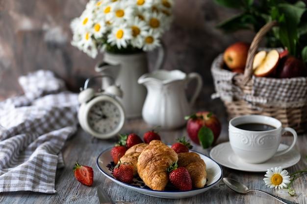 Cornetti con fragole rosse fresche con una tazza di caffè su un tavolo di legno e bouquet di margherite in una brocca.
