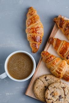 Cornetti con tazza di caffè, biscotti piatti distesi su intonaco e tagliere