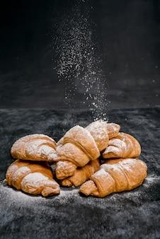 Cornetti con zucchero a velo sul tavolo grigio.