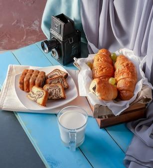 Cornetti e torta alla vaniglia sul tavolo con un bicchiere di latte.