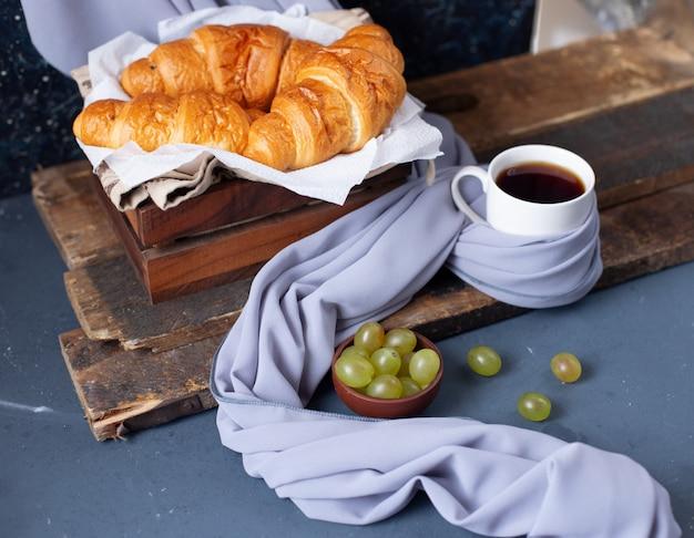 Cornetti e uva verde con una tazza di caffè espresso sul tavolo blu