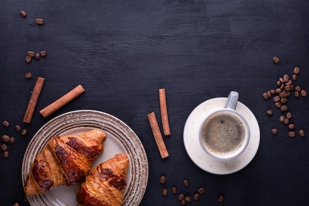 Cornetti su un piatto di ceramica, una tazza di caffè, bastoncini di cannella e chicchi di caffè su un tavolo di legno nero.