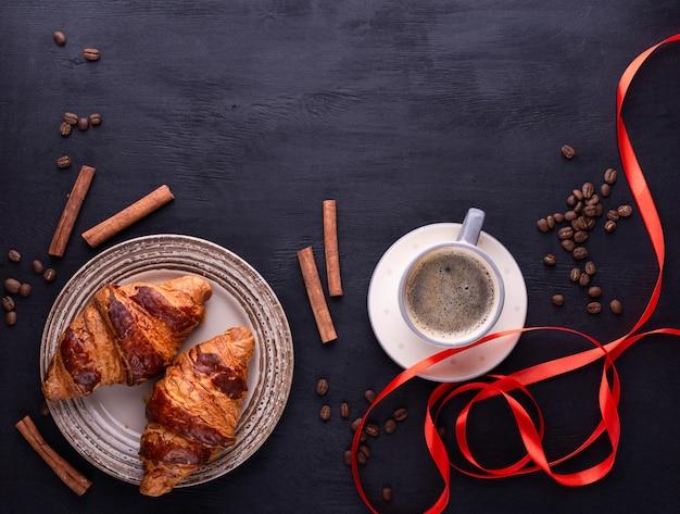 Cornetti su un piatto di ceramica, una tazza di caffè, nastro rosso, bastoncini di cannella e chicchi di caffè su un tavolo di legno nero.