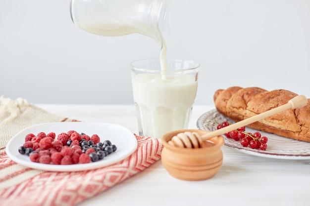 Cornetti sul piatto sul bordo di legno, bacche, caffè, latte e miele su una tovaglia bianca. la mano maschio versa il latte in un bicchiere con caffè. stile di vita. copia spazio