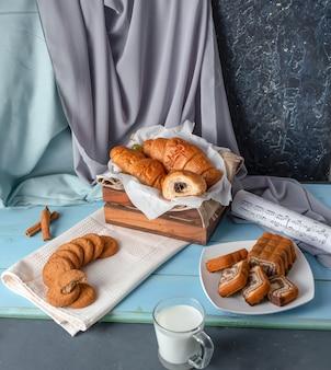 Cornetti, torta a fette e biscotti con una tazza di latte sul tavolo di legno blu.