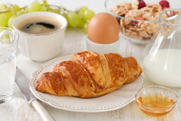 Cornetto con latte, uova, caffè su superficie di legno bianco