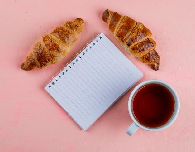 Cornetto con taccuino, tè piatto disteso su un tavolo rosa
