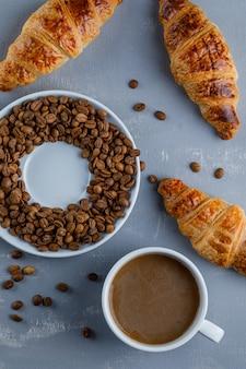 Cornetto con tazza di caffè, chicchi di caffè, piatto disteso.