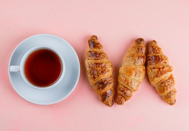 Cornetto con una tazza di tè piatto disteso su un tavolo rosa