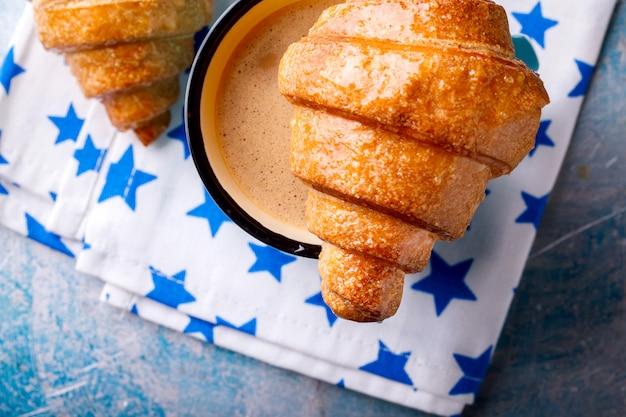 Cornetto e caffè con latte. colazione al forno fresco.