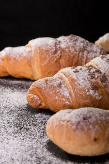 Cornetto grande e piccolo con cioccolato e zucchero a velo sul nero. dessert francese.
