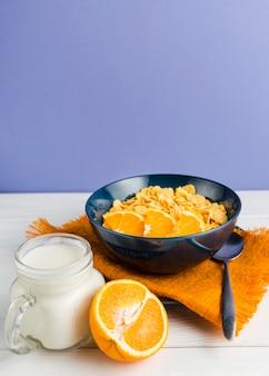 Cornflakes ad alto angolo con arancia e yogurt
