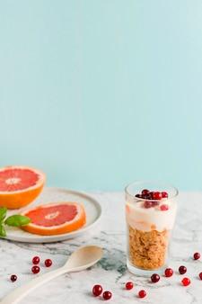 Cornflakes ad alto angolo con yogurt e agrumi in vetro