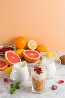 Cornflakes ad alto angolo e yogurt in vetro con mik di frutta