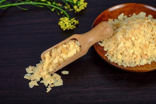 Cornflakes in un cucchiaio di legno su uno sfondo di legno scuro e copia