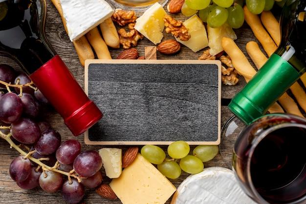 Cornice accanto a bottiglie di vino e uva e formaggio