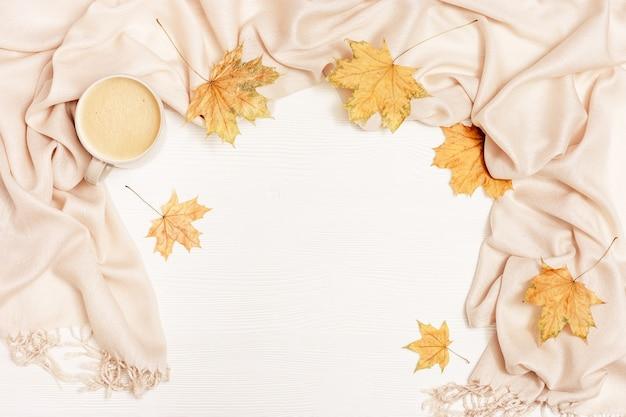 Cornice accogliente autunnale con foglie essiccate di acero e sciarpa beige pastello