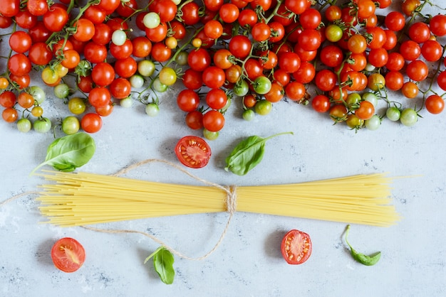 Cornice alimentare. concetto di ingredienti di pasta. spaghetti e pomodoro ciliegia crudi con basilico verde su un fondo blu. vista dall'alto con spazio di copia. cibo italiano