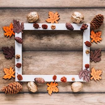 Cornice autunnale di foglie e coni