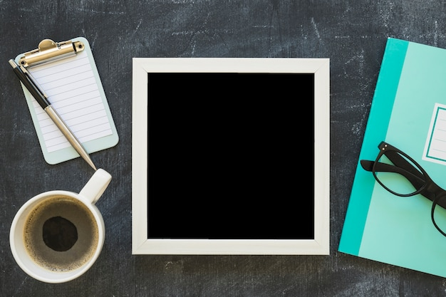 Cornice bianca del bordo; tazza di caffè e cartolerie sulla lavagna