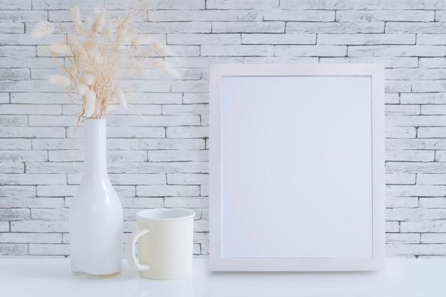 Cornice bianca del modello, vaso di vetro con il fiore del fieno e tazza gialla sulla tavola bianca
