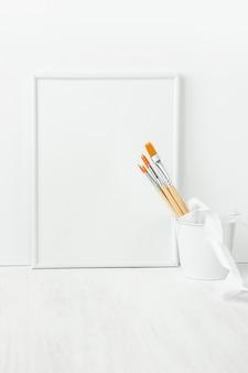 Cornice bianca mock up con pennelli legati con nastro di seta nel secchio