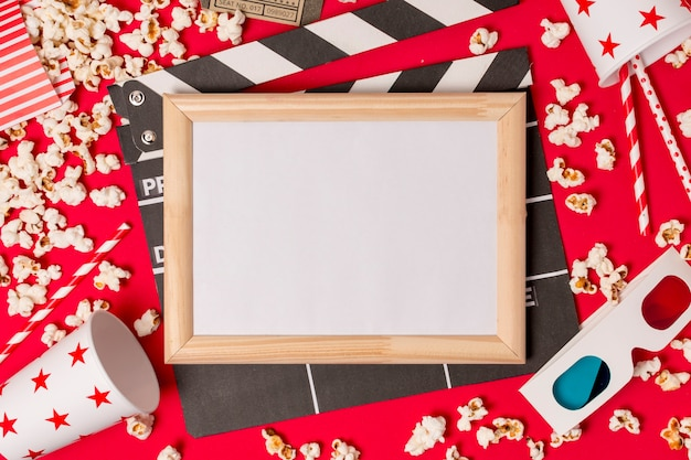 Cornice bianca sopra il ciak con popcorn; cannucce e occhiali 3d su sfondo rosso