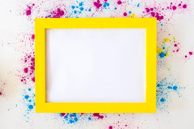 Cornice bianca vuota con bordo giallo su polvere di colore holi su sfondo bianco
