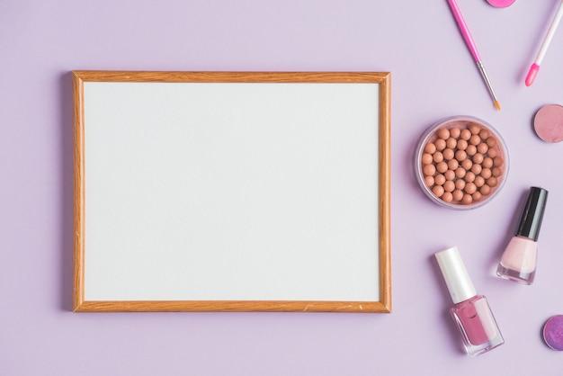 Cornice bianca vuota con prodotti cosmetici su sfondo viola