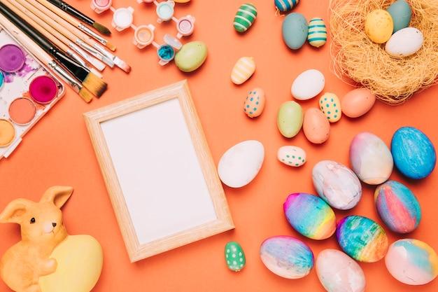 Cornice bianca vuota con uova di pasqua colorate; pennelli; statua di acquerello e coniglio su uno sfondo arancione