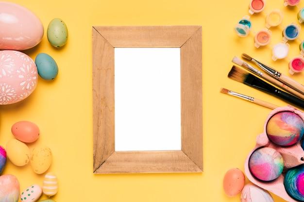 Cornice bianca vuota di legno con uova di pasqua; pennelli e pittura ad acquerello su sfondo giallo