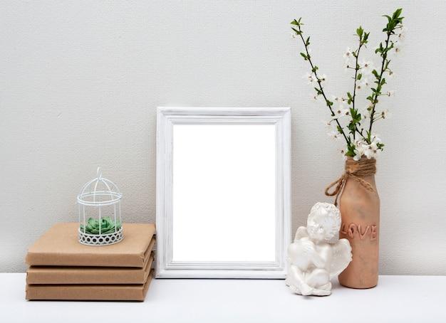 Cornice bianca vuota (mock-up) con un vaso e libri sul tavolo. mock-up di primavera per il tuo testo.
