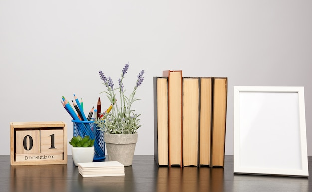 Cornice bianca vuota, pila di libri e una pentola di lavanda in crescita su un tavolo nero