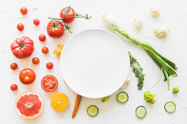 Cornice bianca vuota sopra le verdure colorate su sfondo strutturato