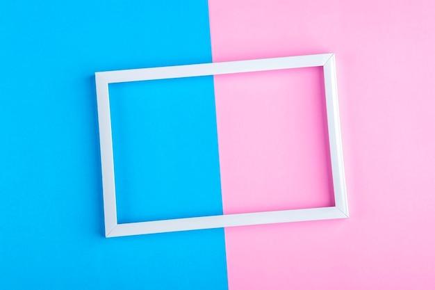 Cornice bianca vuota su uno sfondo a due tonalità (blu, rosa) con spazio di copia per testo o lettere. composizione minimale di linee geometriche. vista dall'alto, piatto, mock up.