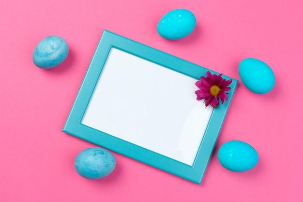 Cornice blu e uova su sfondo rosa