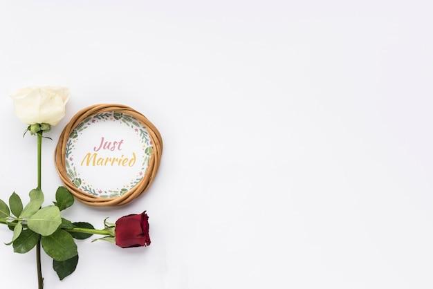 Cornice circolare con testo e fiori appena sposati su superficie bianca